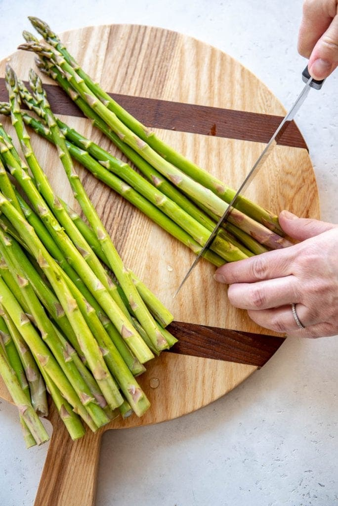 Woman cutting asparagus on a wooden cutting board