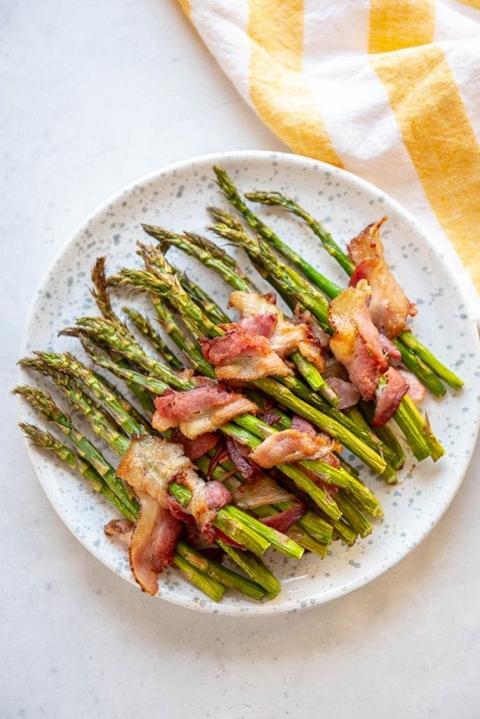 Asparagus wrapped in bacon on a white plate