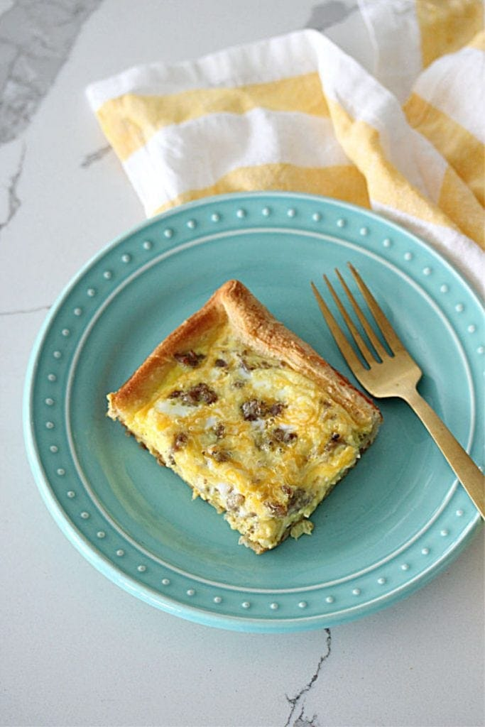 A piece of breakfast casserole on a teal plate with a gold fork and a white and gold napkin