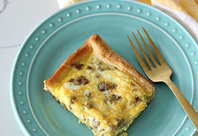 Piece of breakfast casserole on a teal plate with a gold fork and a white and yellow napkin