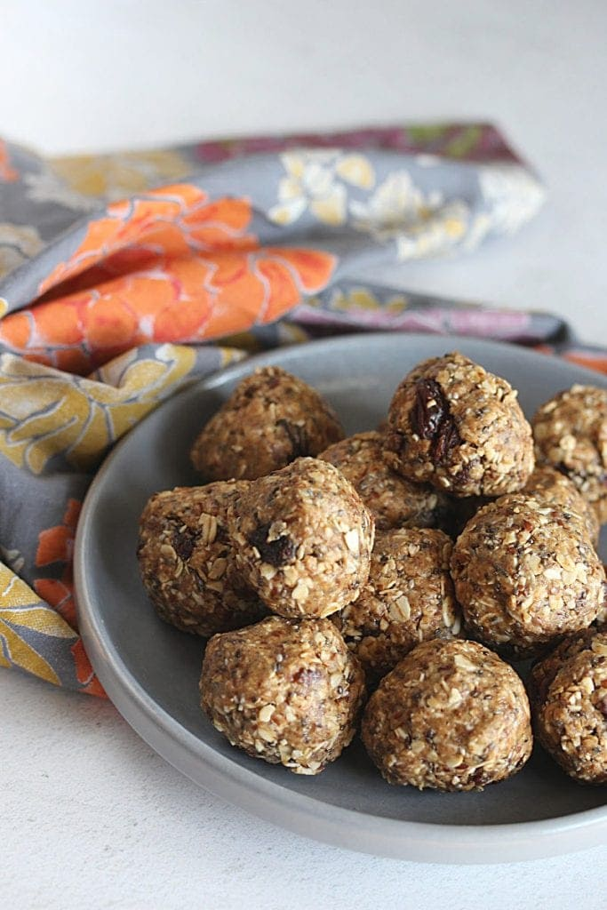 Picture of oatmeal raisin protein balls on a grey plate with a floral napkin