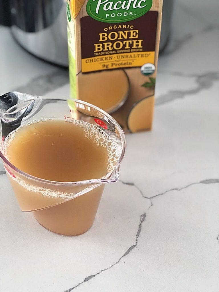 A measuring cup with chicken bone broth in it with a box of bone broth next to it.