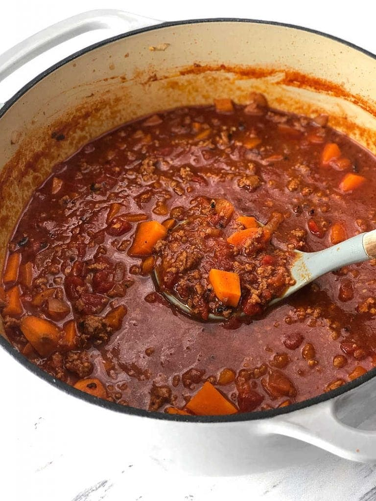 Large bowl of dutch oven chili and a ladle with a serving of chili