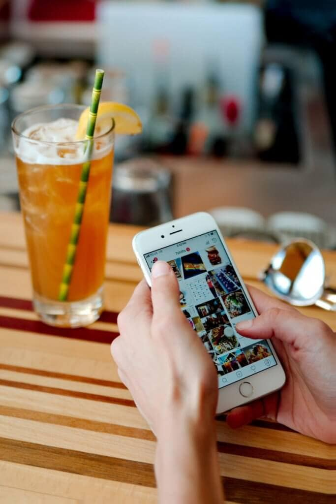 A woman holding a phone with an iced tea in the background