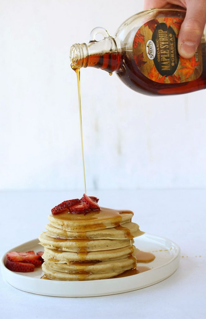 A person pouring maple syrup on a stack of pancakes