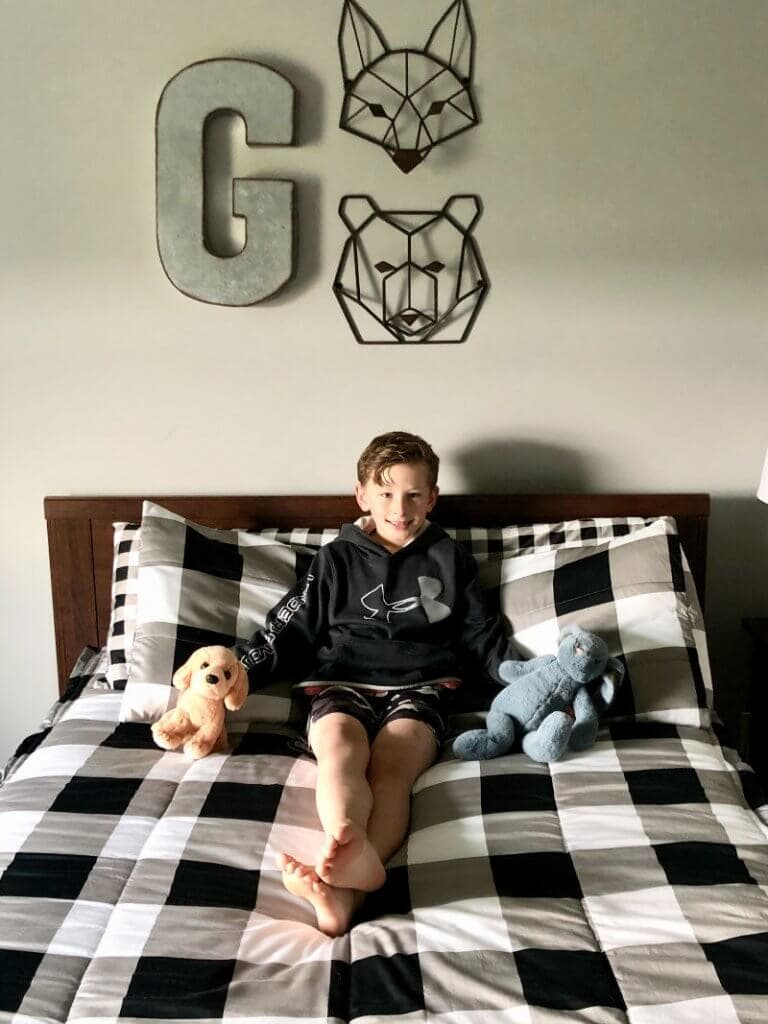 A boy smiling on top of his beddy's bed.