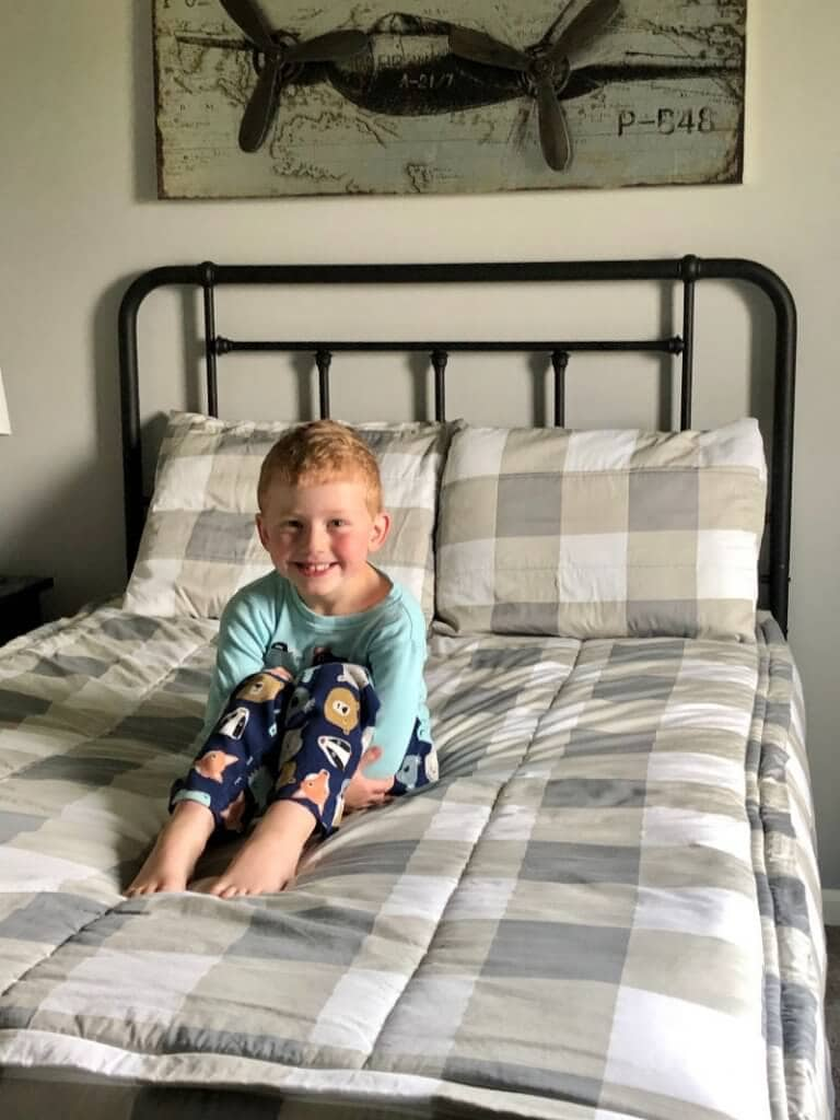 a young boy smiling on top of his bed