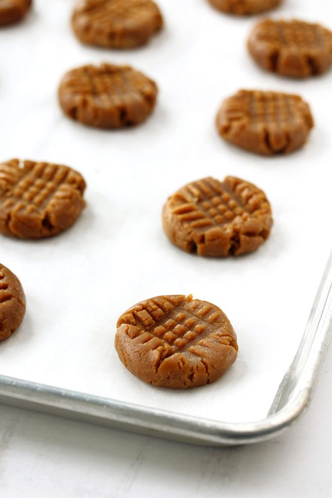 A baking sheet lined with flourless peanut butter cookies ready to be baked.
