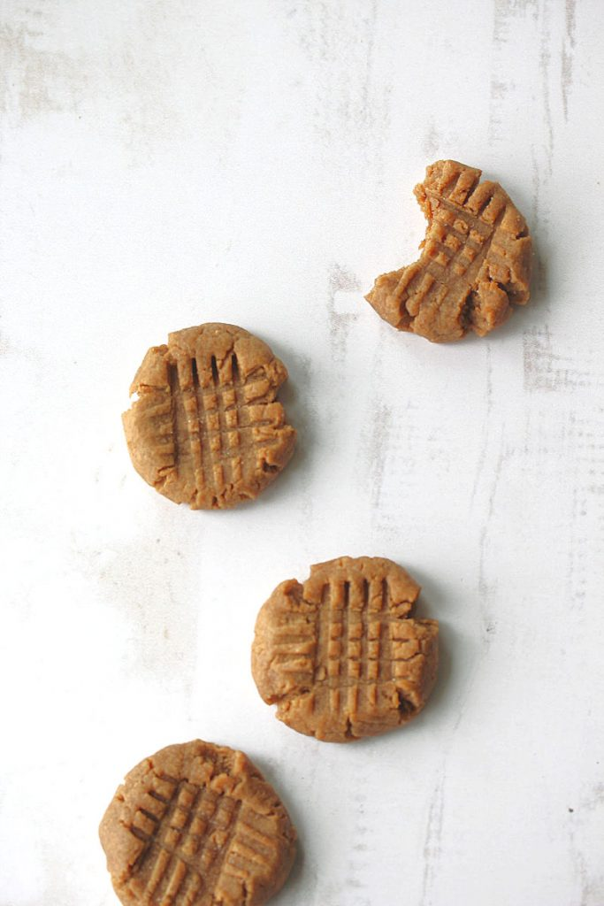 4 flourless peanut butter cookies with one missing a bite out of it