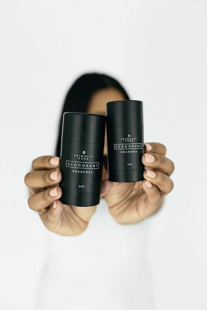 A woman with dark hair holding 2 bottles of primally pure charcoal deodorant over her face.