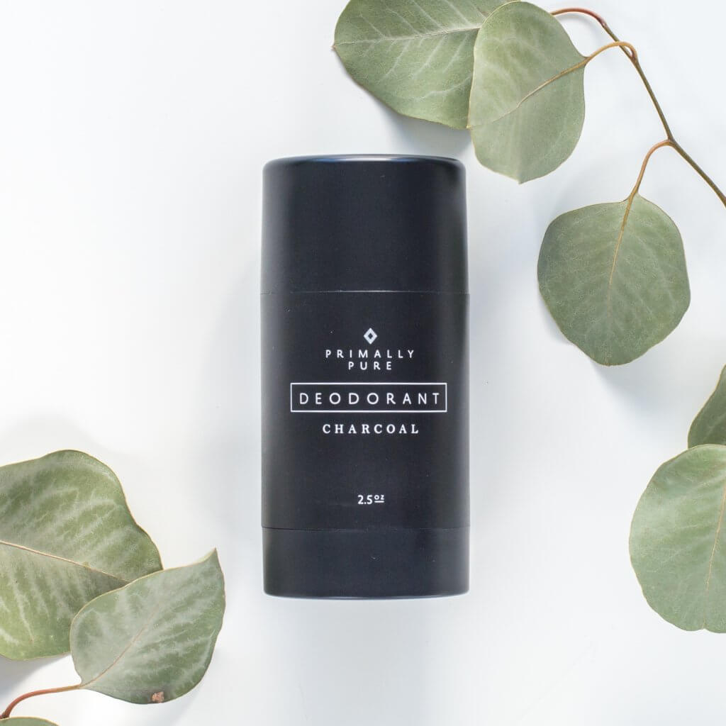 A bottle of primally pure charcoal deodorant with green leaves on a white background