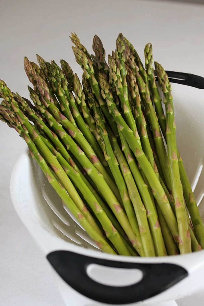 Wash a bunch of asparagus in a white strainer