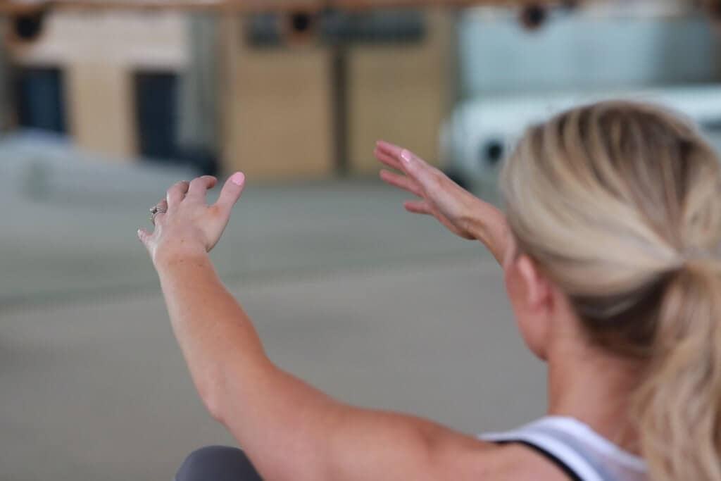 A woman with her arms outstretched doing a workout routine