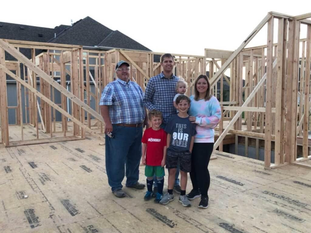 a family standing inside their dream home with the walls just framed