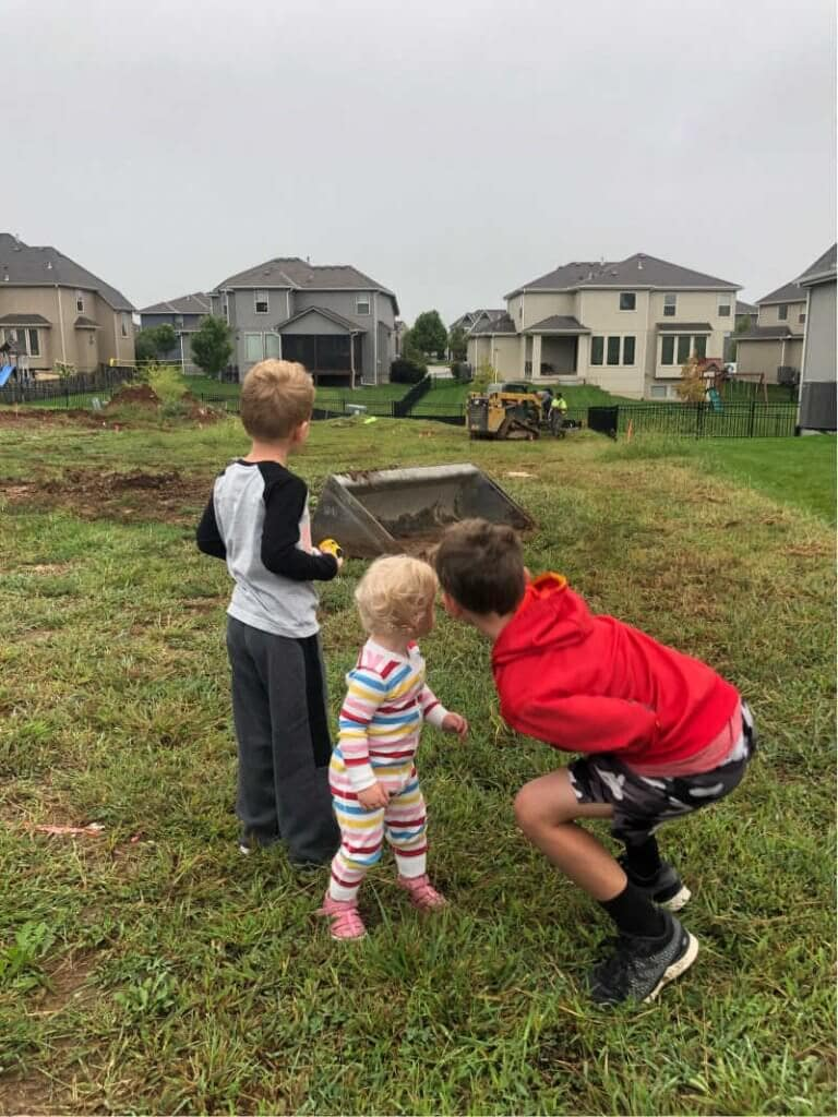 3 Kids pointing at an empty lot where their house will be built
