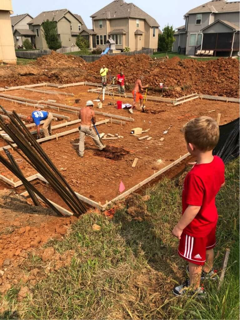A child looking at a dirt pile and men putting up a basement foundation