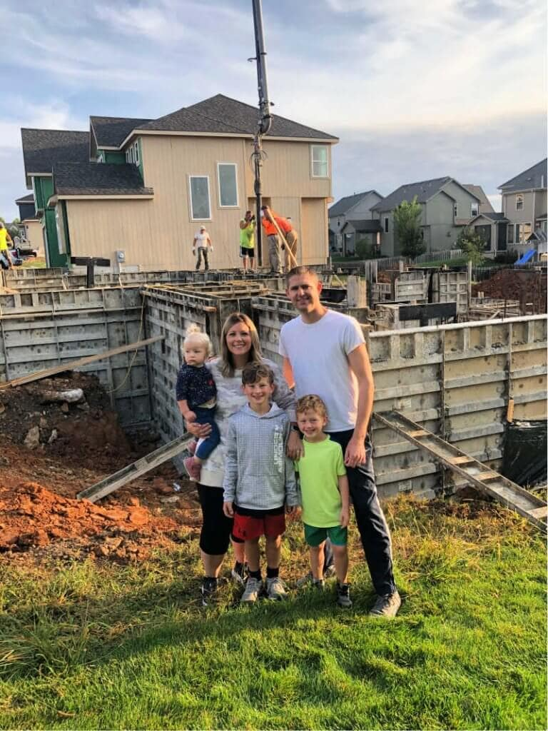 A family standing in front of the basement of their future home