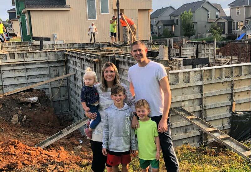 a family posing for a picture in front of the basement of their dream home