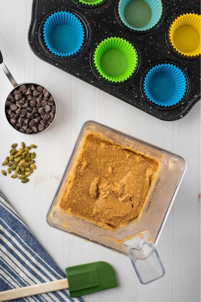 pumpkin muffin batter in a blender with chocolate chips and pumpkin seeds with a muffin tin ready and lined
