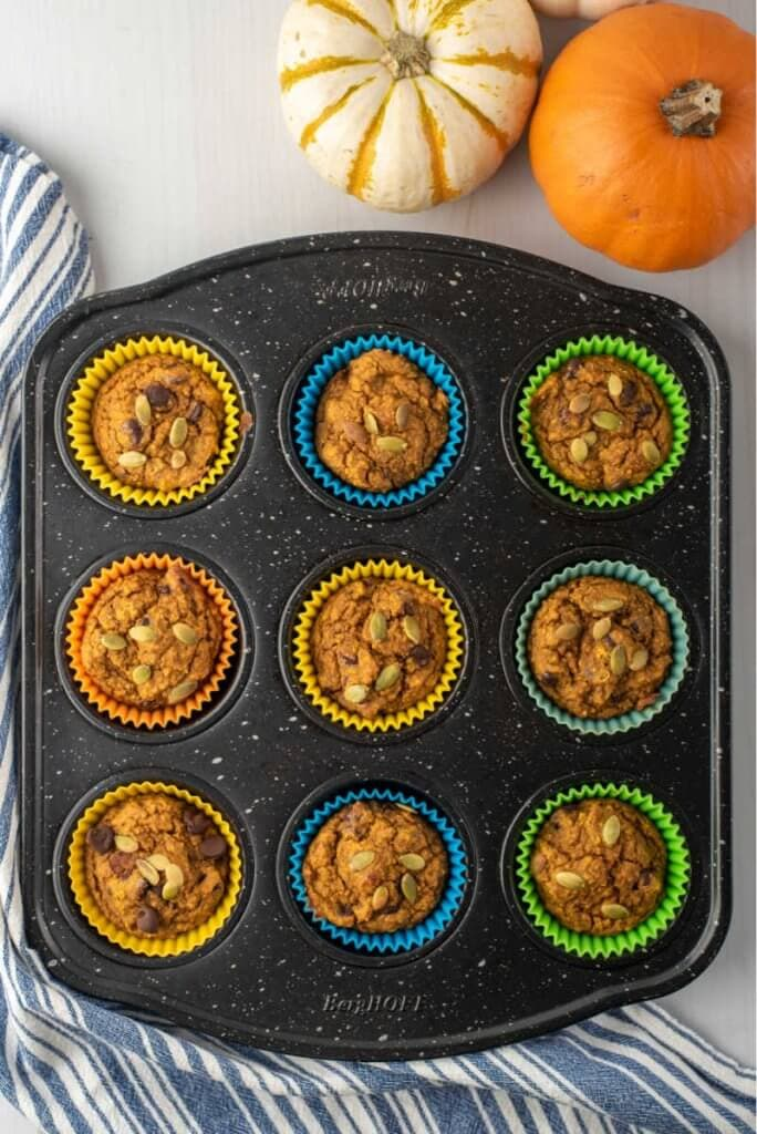 a muffin tin with baked healthy pumpkin muffins in them