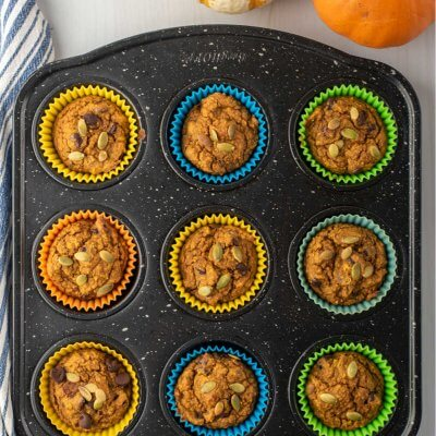Healthy Pumpkin muffins in a black muffin tin with muffins and a napkin
