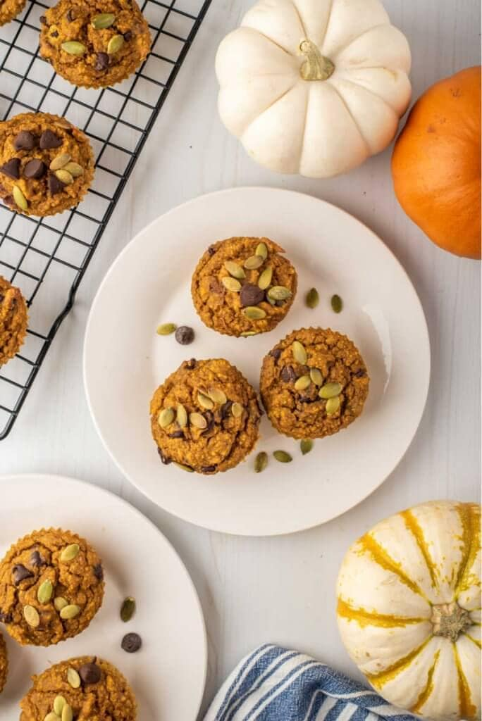 plated healthy pumpkin muffins on white plates with pumpkins and a napkin