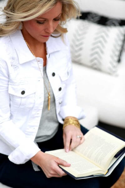 Woman reading a book in a white jacket