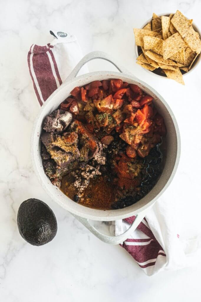 A stock pot of creamy taco soup with tortilla chips and an avocado