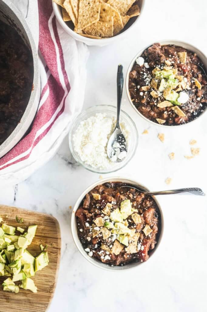 2 bowls of creamy taco soup by a bowl of goat cheese, avocado and tortilla chips