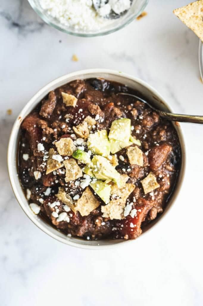 Bowl of creamy taco soup topped with avocado and goat cheese
