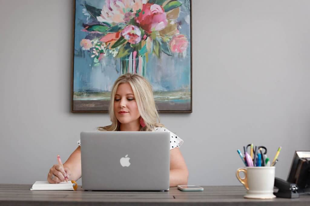 A woman sitting at her desk with her MacBook and writing notes