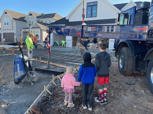three children looking at a driveway being poured