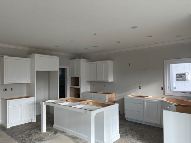 A white kitchen prior to having countertops installed in a new construction home