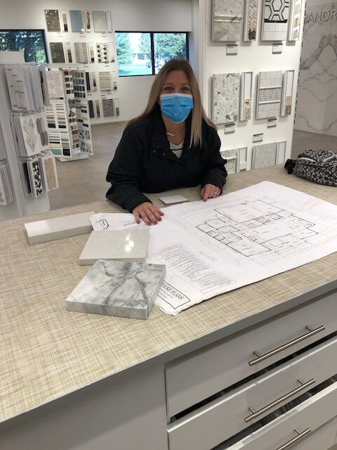 A woman with a set of house plans at a design studio