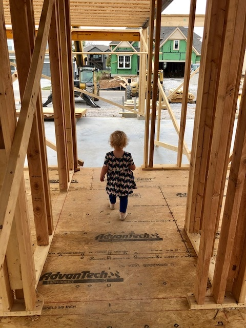 A toddler girl walking through a home that has just been framed
