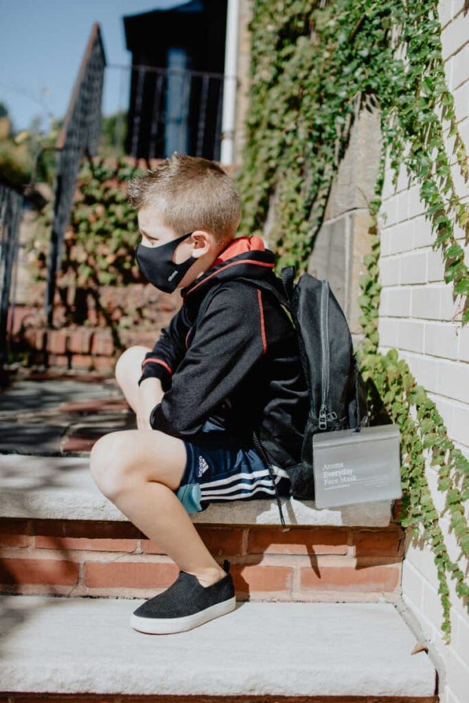 A boy ready for school with a mask on his face