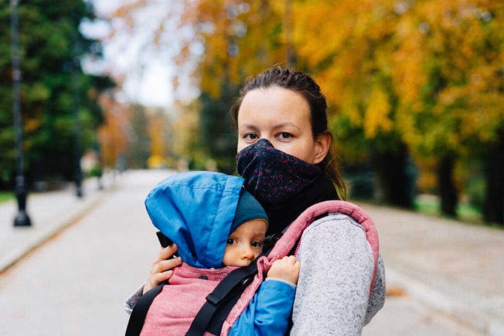 Woman with a face mask on holding her child