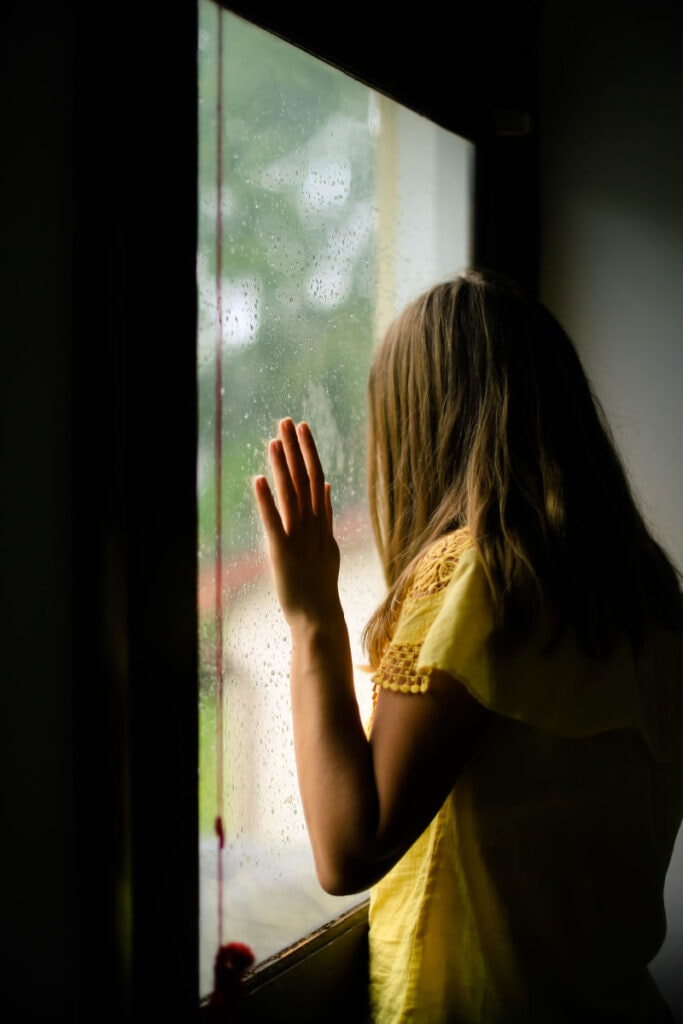a woman looking out a window with her hand on the glass