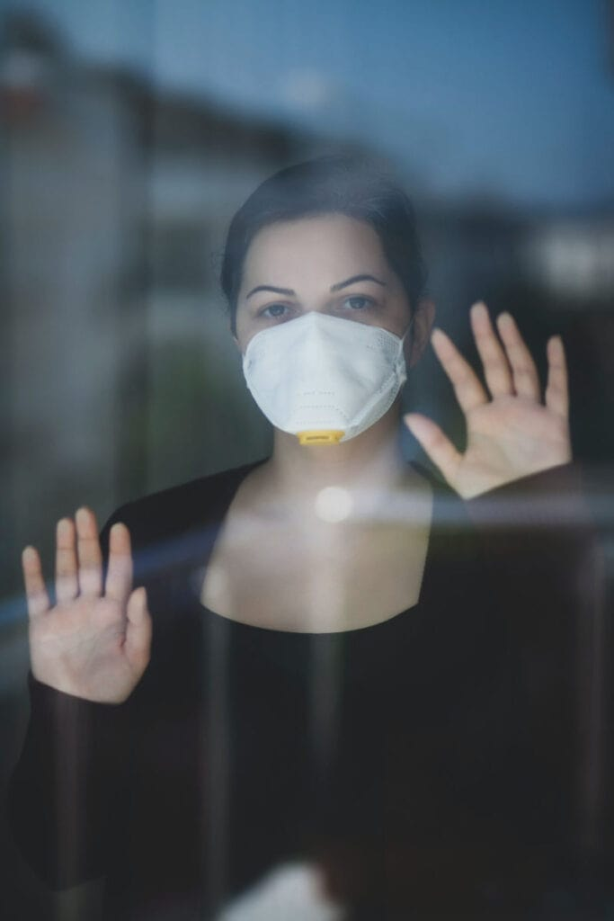 a woman with a face mask on looking out the window with her hands on the glass