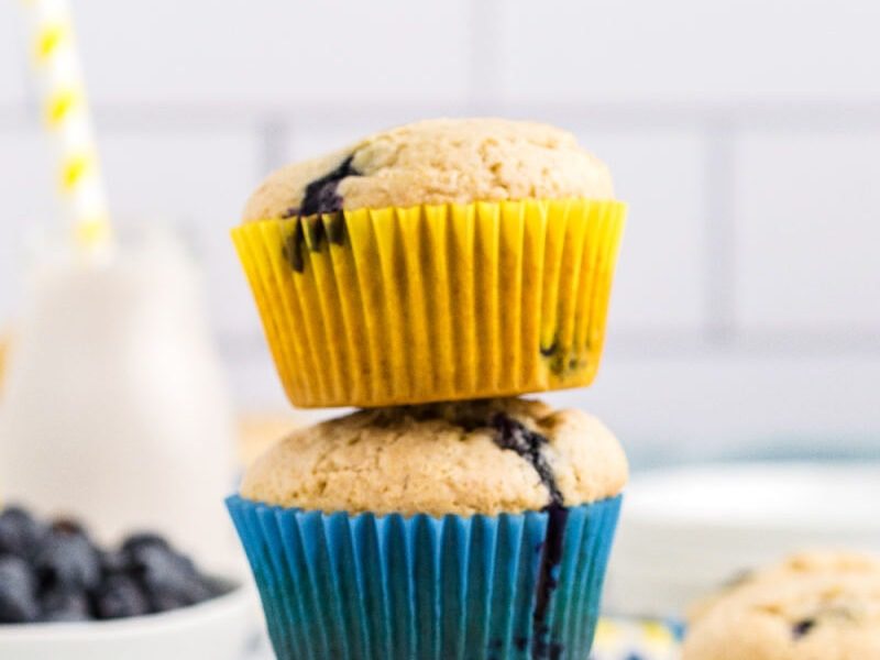 A stack of 3 lemon blueberry muffins with yellow and blue liners