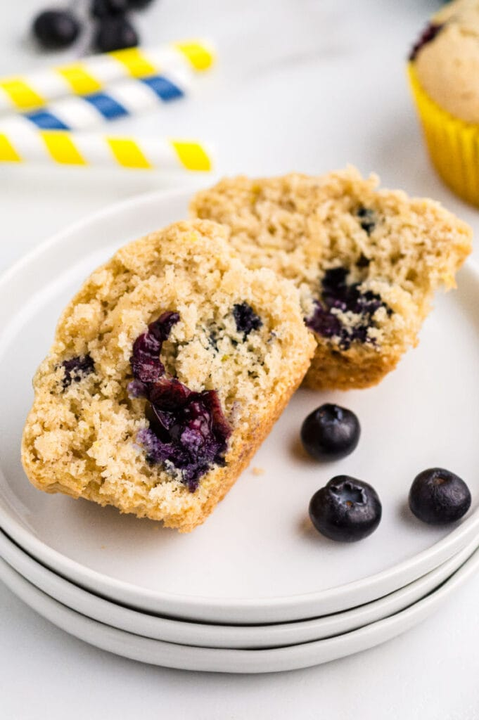 A lemon blueberry muffin on a white plate cut in half with a few blueberries on the plate